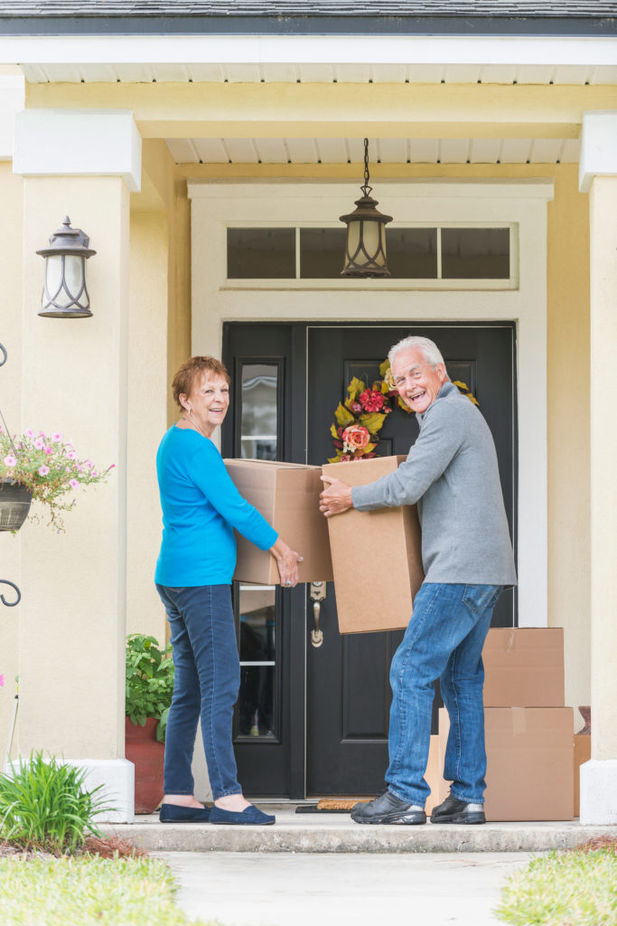 Couple Moving Boxes Outside of their Home