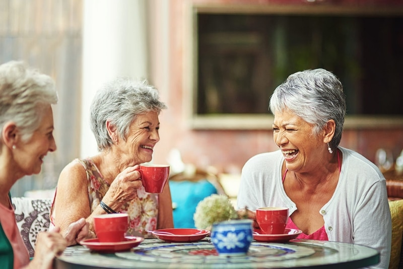 Older Ladies Drinking Coffee and Laughing